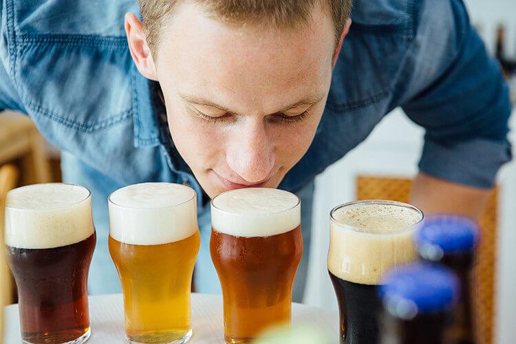 Mann schnuppert an Bier