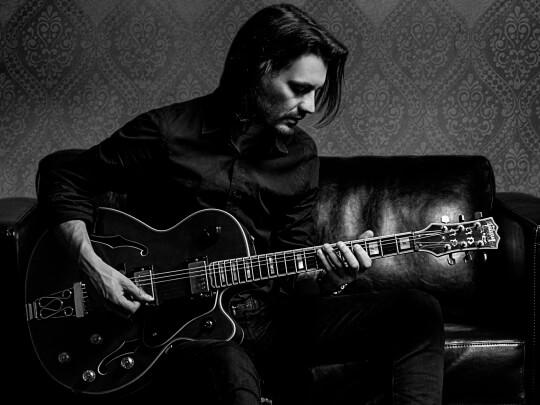 Künstlervermittlung: Gitarrist Victor in schwarzweiß auf dem Sofa Frankfurt - Künstleragentur | DIE ALLESLÖSER