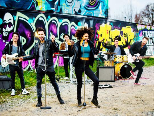 junge Musiker vor Grafíttimauer
