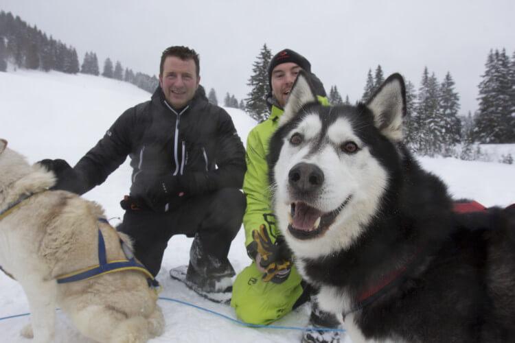 Männer mit Huskys im Schnee