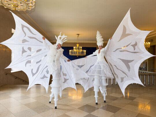 Künstlervermittlung: Rottaler Staatzirkus auf Stelzen in weißen Kostümen Frankfurt - Künstleragentur | DIE ALLESLÖSER