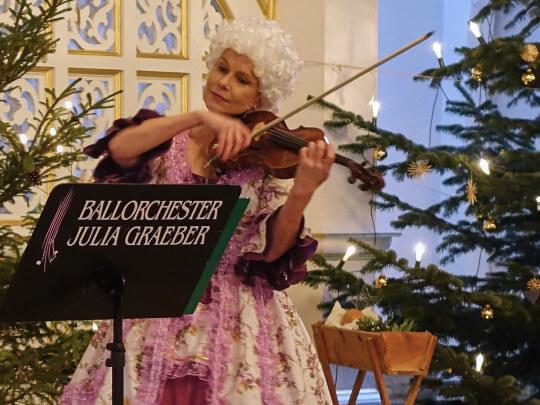 Künstlervermittlung: Julia Graeber Weihnachtsprogramm neben einem Christbaum Frankfurt - Künstleragentur | DIE ALLESLÖSER