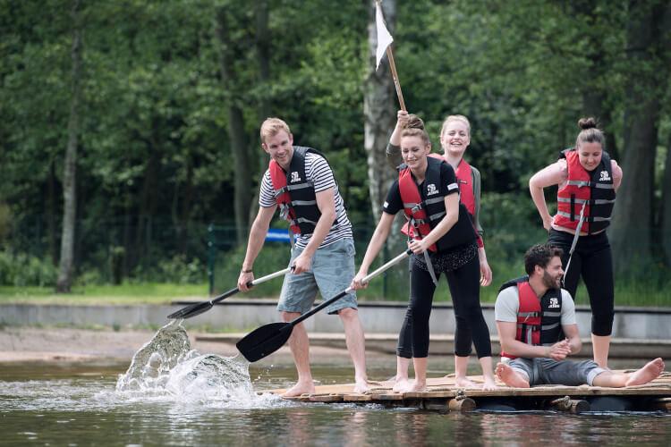 Floßbau Team paddelt mit Flagge