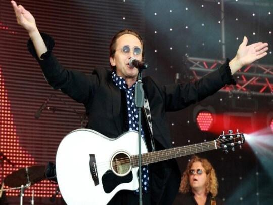 Marius Müller Westernhagen Double mit Händen oben und Gitarre