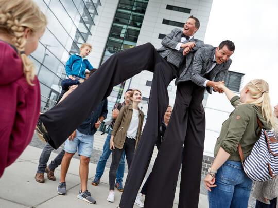 Künstlervermittlung: Klirr Deluxe auf Stelzen in einer Menschenmenge Frankfurt - Künstleragentur | DIE ALLESLÖSER