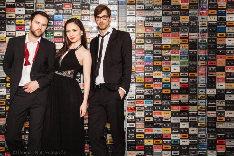 Kassettendeck Trio stehend vor einer Wand aus Kassetten