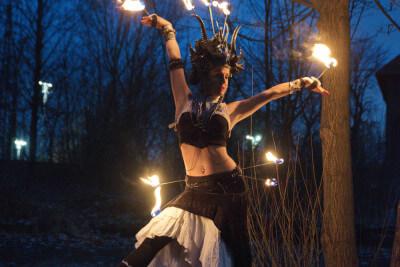 Krisztina Toth mit brennendem Kranz auf Podest vor Baum