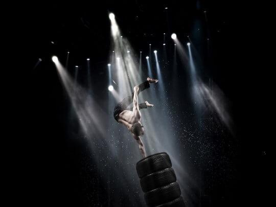 Mann im Handstand auf Reifen im Licht mit Regen