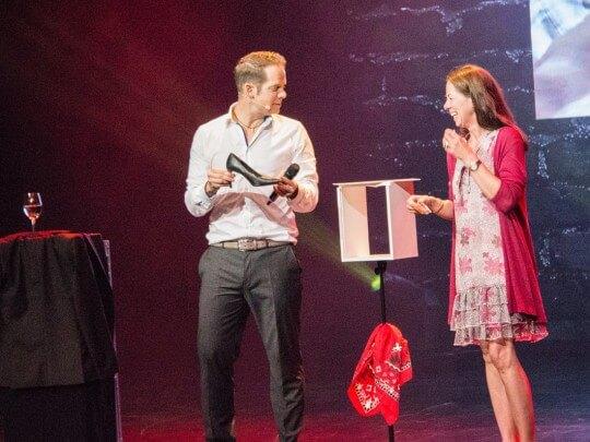 Künstlervermittlung: Marco Brüser mit Damenschuh und Frauauf einer Bühne Frankfurt - Künstleragentur | DIE ALLESLÖSER