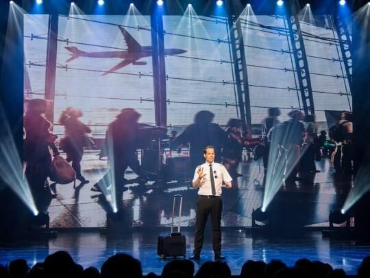 Künstlervermittlung: Marco Brüser als Pilot auf der Bühne mit Flughafen in Projektion Frankfurt - Künstleragentur | DIE ALLESLÖSER