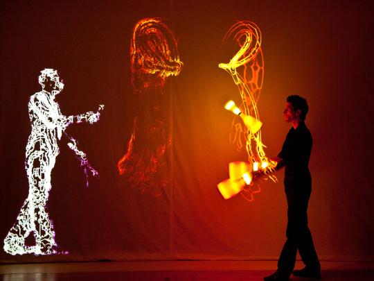 Jongleur mit Spiegelbild aus Licht