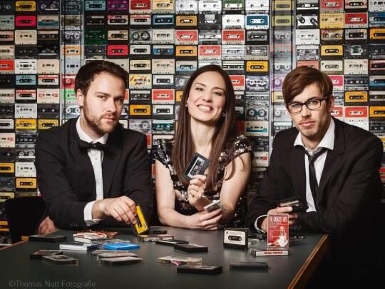 Künstlervermittlung: Kassettendeck-Band an einem Tisch mit Kassetten in der Hand Frankfurt - Künstleragentur | DIE ALLESLÖSER