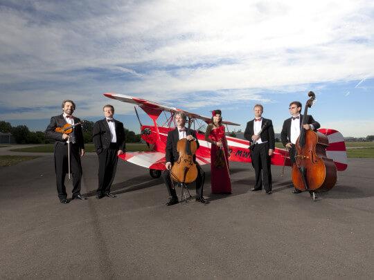 Künstlervermittlung: Orchester Salonissimo vor Flugzeug Frankfurt - Künstleragentur | DIE ALLESLÖSER