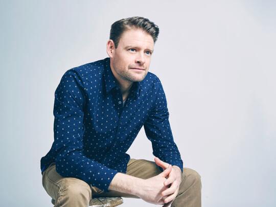 Künstlervermittlung: Max Giermann sitzend Frankfurt - Künstleragentur | DIE ALLESLÖSER