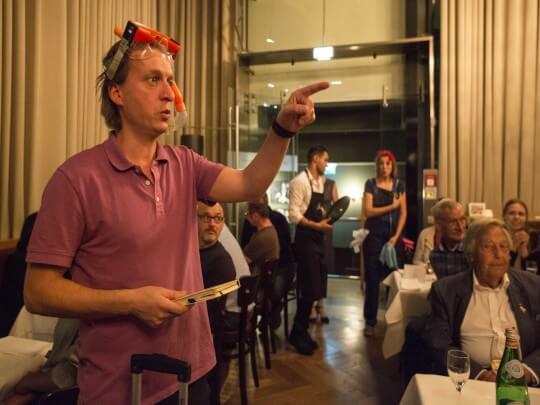 Künstlervermittlung: Mann im rosafarbenenen Polohemd zeigt auf etwas Frankfurt - Künstleragentur | DIE ALLESLÖSER
