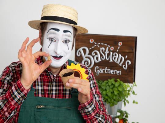 Künstlervermittlung: Pantomime Bastian mit einem Samen in der Hand Frankfurt - Künstleragentur | DIE ALLESLÖSER