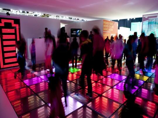 Menschen auf einer bunten Tanzfläche.